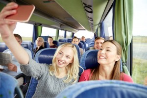 59097637 - transport, tourism, road trip and people concept - happy young women or friends in travel bus taking selfie by smartphone
